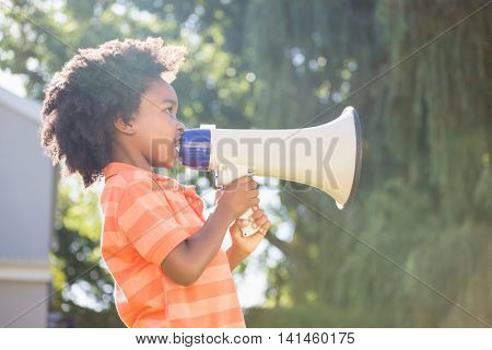 Cute mixed-race boy speaking on a megaphone on a park