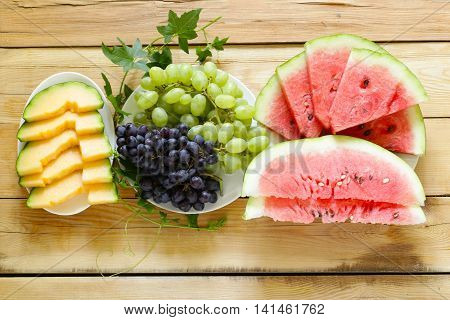 ripe organic fruit watermelon, melon cantaloupe and grapes on a wooden table, top view