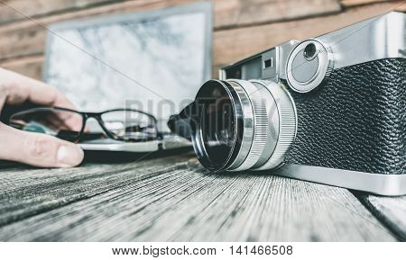 Photographer working outdoor on wooden table next his old retro camera - Essential kit for young hipster man - Photography editing and technology process concept - Vintage desaturated filter