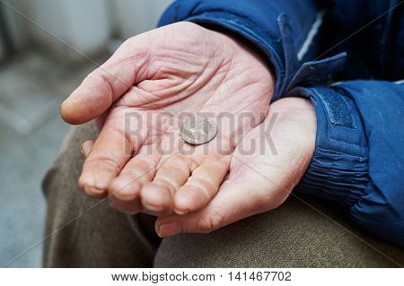hands of beggar with us cent coin begging for money