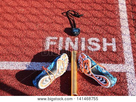 A set of spikes, a baton and a stopwatch at the finish line on a track,
