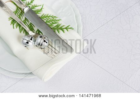 Christmas table with silver knife and fork jingles and green thuja branches lie on the white porcelain plate which is located on a table covered with a white tablecloth top view