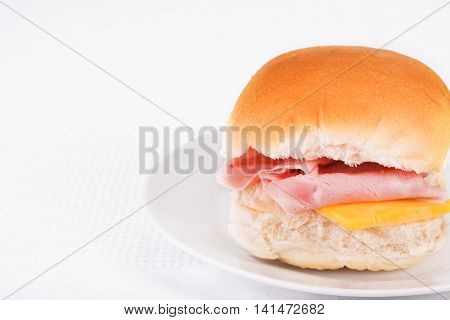 Ham and cheese bread roll or bap on a white plate