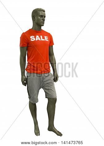 Male mannequin dressed in shorts and red t-shirt on which sale is written. No brand names or copyright objects.