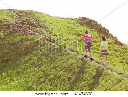 Two fit young women friends exercising in a park running up the hill. Active healthy lifestyle and outdoor workout concept