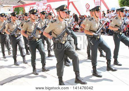 Magdalena Cajamarca Peru - July 25 2016: Policemen with machine guns march in town festival in Magdalena Cajamarca Peru on July 25 2016