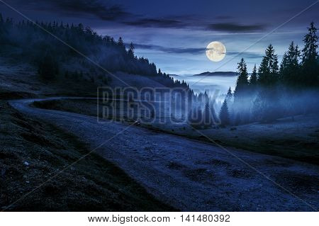 Road Near Foggy Forest In Mountains At Night
