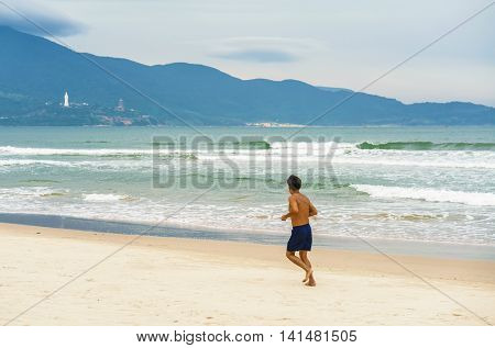 Danang. Vietnam - February 20, 2016: Man running near the China Beach in Danang in Vietnam. It is also called Non Nuoc Beach. South China Sea and Marble Mountains on the background.