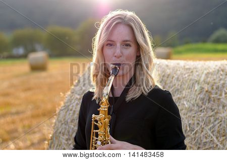 Attractive Young Woman Playing A Tenor Saxophone