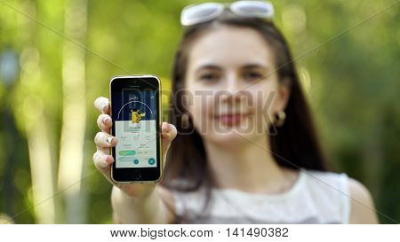 Samara, Russia - August 6, 2016: woman playing pokemon go on his iphone. pokemon go multiplayer game with elements of augmented reality. Catching the Pikachu pokemon.