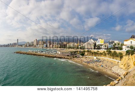 BENIDORM SPAIN - OCTOBER 06 2014: People relaxing on the beach of Mediterranean resort Benidorm province of Alicante Spain