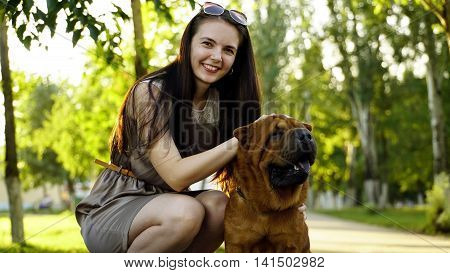 young woman walking in the park with a Shar-Pei.