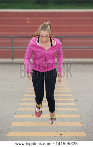 Pretty blond looking down while running up stadium.