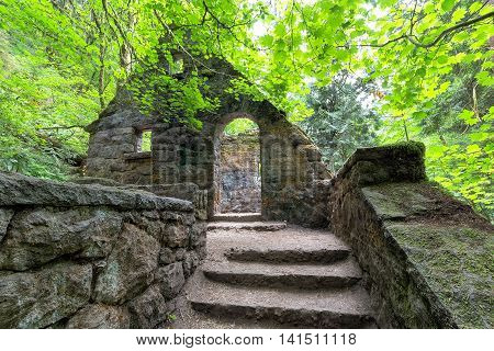Abandoned stone castle house framed by Maple Trees at Wildwood Trail in Forest Park Portland Oregon