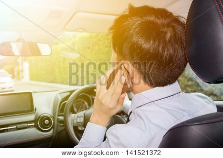 Asian Businessman Talking On Phone While Driving