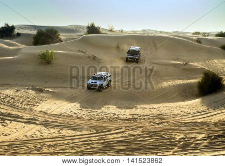 DUBAI UNITED ARAB EMIRATES - JANUARY 25 2016: Safari rally Hummer H2 car 4x4 adventure driving in the desert sand dune is a popular activity among tourists in Dubai.