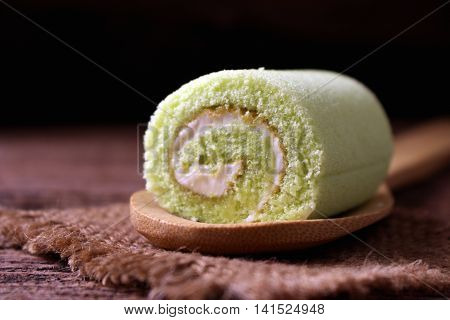 rool cake on wooden spoon green tea roll cake close up