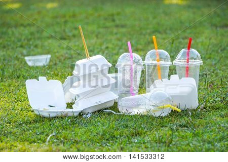 foam and plastic food container on grass field - environmental problems