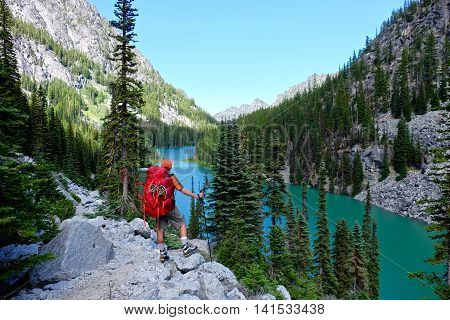 Man hiker by alpine lake. Nada lake,  Enchantment Lakes basin,  Leavenworth,  Seattle,  Washington state,  USA .