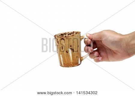 Hand holding a dirty cup of coffee after heating in a microwave oven