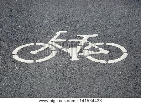 Bike lane sign / white bicycle symbol on the black road