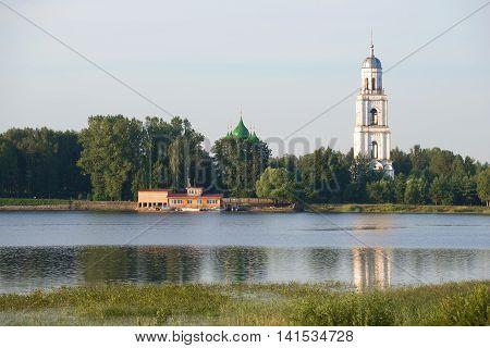 The old bell tower of the assumption Church over the river Sogozha, july morning. Poshekhon'ye, Yaroslavl region, Russia