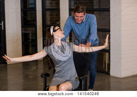 Happy man pushing female colleague sitting on chair in creative office