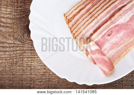 Appetiser From Slices Of Bacon On Plate On Wooden Plank