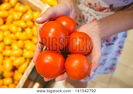 Girl's hand holding a sprig of tomatoes in the store. Picking the tomatoes among the vegetables in the supermarket. Red fresh tomatoes. Vegetarian food fresh and raw.
