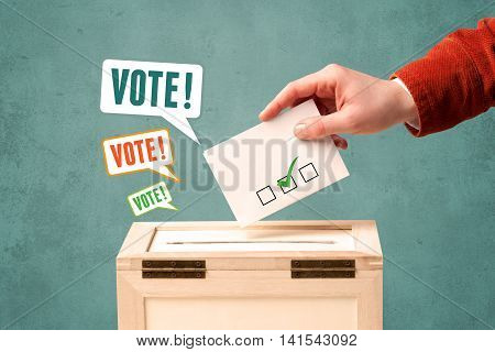 A hand placing a voting slip into a ballot box