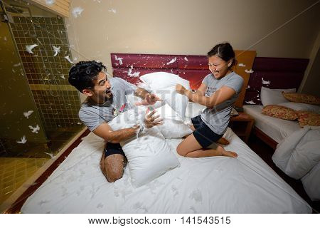 happy loving asian couple having a pillow fight in bed at night