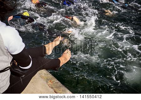 FREDERICIA DENMARK - AUGUST 6 2016: Female spectator with tattoo on the foot looks triathlon competition Challenge Denmark in Fredericia Old harbor August 6 2016.