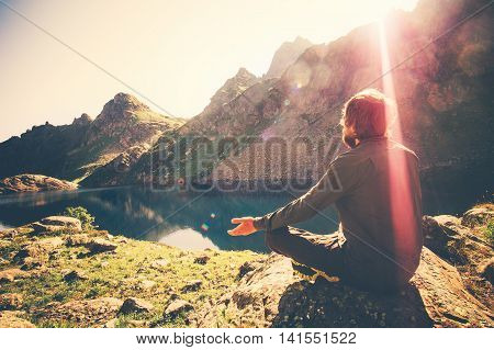 Bearded Man meditating yoga relaxing alone sitting lotus pose on stone Travel healthy Lifestyle concept lake and mountains sunny landscape on background outdoor