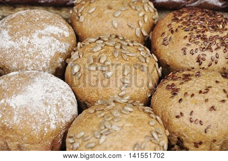 Seven round buns with sunflower seeds and sesame seeds.
