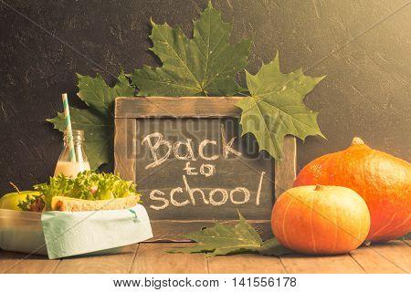 autumn still life with chalkboard, lunchbox and pumpkins on dark background
