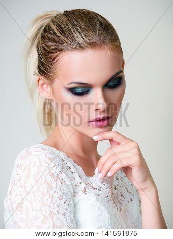 Studio fashion shot: a beautiful young girl in white dress