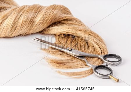 Hairdresser's scissors with strand of blond hair on a white background