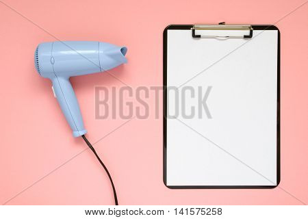 Blue hair dryer and clipboard on pink paper background