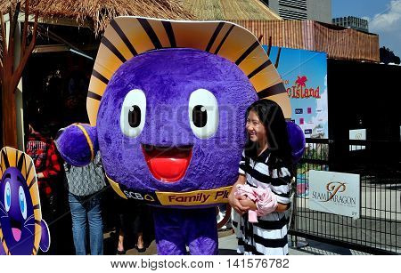 Bangkok Thailand - January 11 2013: Young Than woman posing with the purple SCB mascot on Children's Day at the upscale Siam Paragon shopping center