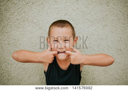 Boy standing in front of wall making funny faces