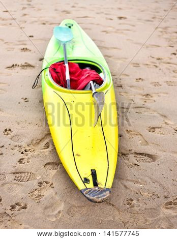 Multicolored canoe on the beach. Selective focus of a yellow and green canoe boat. Focus on the foreground and copy space.