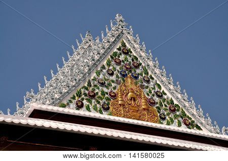Bangkok Thailand - December 26 2011: Detail of ornate roof tympanum with porcelain floral motifs and gilded bas relief designs at Royal Wat Boworniwet