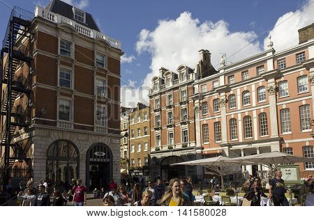 LONDON, UNITED KINGDOM - SEPTEMBER 12 2015: Covent Garden Piazza in London building around and people