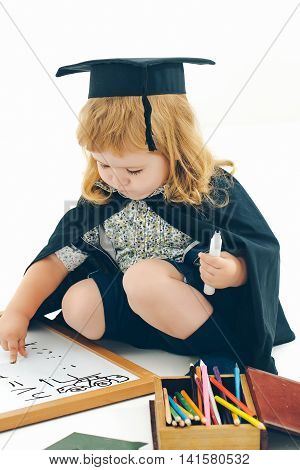Little boy child in black academic gown and squared hat playing with drawing school board holding marker near box with colored pencils isolated on white background