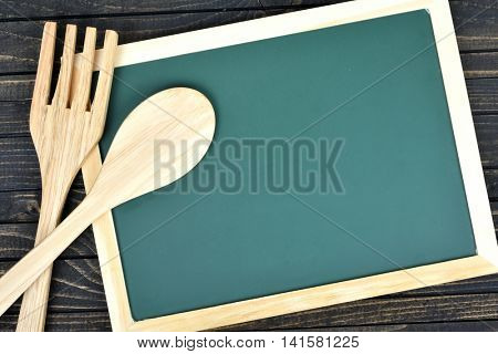 Kitchen utensils and green board on wooden table