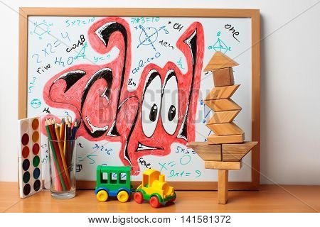 school text word painted graffiti with smiley eyes math equations and formulas on paper near colorful pencils in glass plastic car toy wooden cubes and watercolor paint palette on table