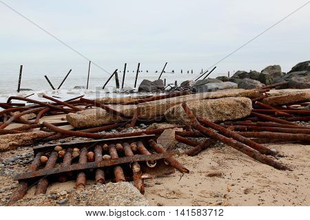 Steel barriers and concrete slabs form coastal defences which have been crushed by nature to allow the sea to erode the coast of Norfolk England
