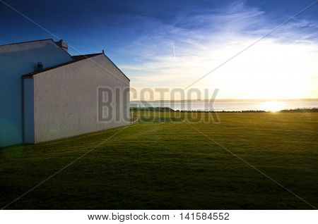 Landscape with modern architecture and garden at sunset