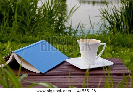 Good place for reading outdoor- garden by the lake. Book and coffee on a park bench.