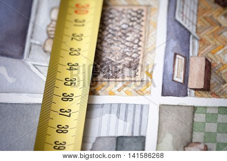 Yellow measuring tape in centimeters shot as macro image on the background of watercolor floorplan sketch painting symbolising artistic approach in designing and building house interior space